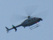Close up of people hanging out lookind down as Army chopper flys over home