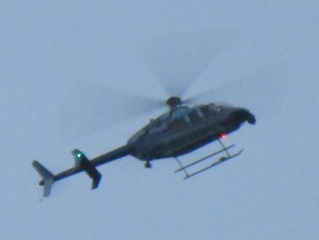 Close up of people hanging out lookind down as Army chopper flys over home.jpg
