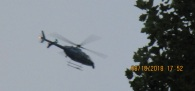 long, nosed, flaps up Army copter low to ground circling home